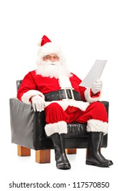 Santa Claus sitting in a comfortable armchair and reading a letter isolated on white background