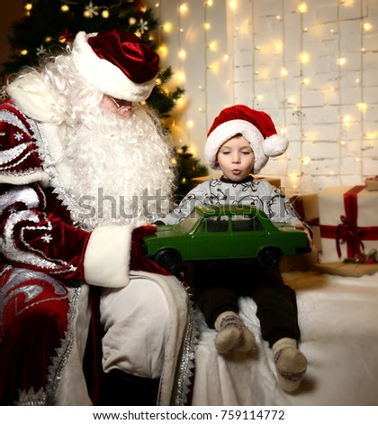 c08cd9fbb9f9 Santa Claus sitting with happy little cute baby boy kid near Christmas tree  at home green