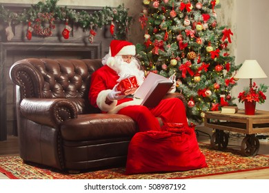 Santa Claus sitting at his home in a comfortable chair and reading letter. Christmas.