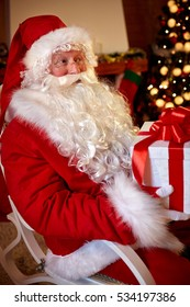Santa Claus sitting and holding big box with Christmas gift