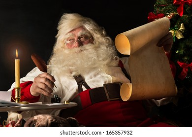 Santa Claus sitting at home and writing on old paper roll to do list with quill pen and ink at night with candle light. Authentic vintage style portrait.