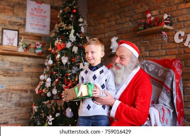 Santa Claus, sitting on armchair, holds small male child lap, cutes boys head sweetly and gives long-awaited surprise in box. kid with pleasure impatience shakes coveted gift runs to unpack present