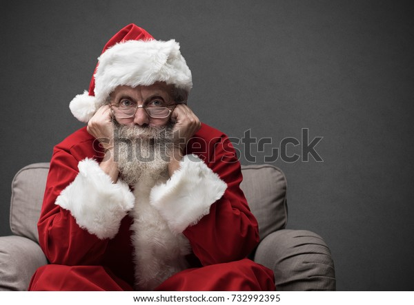Santa Claus sitting on the armchair and waiting for Christmas, he is resting his head on his hands