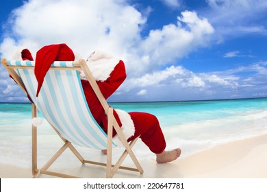 Santa Claus sitting on beach chairs with blue sky and cloud.Christmas Day concept.