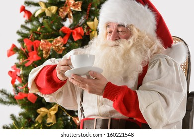 Santa Claus sitting in rocking chair near Christmas Tree at home and drinking hot tea or coffee
