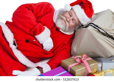 Santa claus sleeping beside christmas present against white background