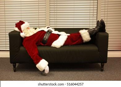 santa claus sleeping on sofa in office