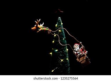 Santa Claus in sleigh with reindeer flying around Christmas tree