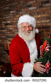 Santa Claus smiling as he is standing next to a Christmas Tree.