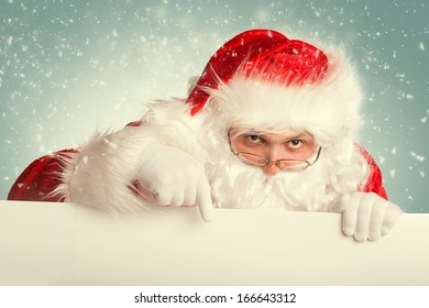 Santa Claus in a snow pointing to white blank banner