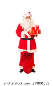 santa claus standing with gifts in hands and sack at his feet