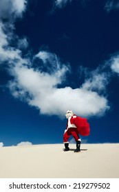 Santa Claus standing on the beach on a sand dune holding a sack full of presents looking at the view