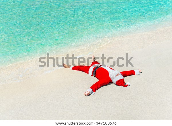 Santa Claus sunbathe on sand in waves at tropical ocean beach, Christmas and New Year winter vacation in hot countries concept