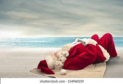 Santa Claus sunbathing lying on the beach