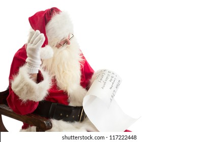 Santa Claus is surprised about the expensive presents on a wish list