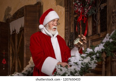 Santa Claus with surprised, shocked face holds alarm clock showing five to midnight on the porch of decorated  house. Time to celebrate concept. Christmas and New Year holidays celebration.