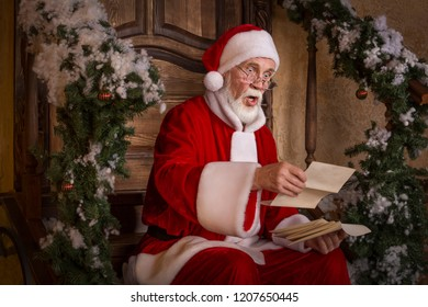 Santa Claus with surprised, worried, shocked face is sitting on the porch of decorated house and reading the letter with list of gifts to deliver. Christmas and New Year holidays celebration.