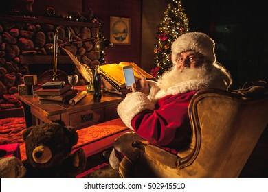 Santa Claus swiping a smart phone with his thumb while smiling at camera