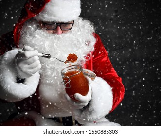 Santa Claus is taking a fork full of red salmon caviar from a big jar, holding a fork with it under the snow. New year and Merry Christmas and happy holidays concept