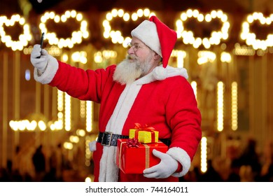 Santa Claus taking a selfie on smartphone. Cheerful Santa Claus with gift boxes taking a picture with smartphone on festive lights background.