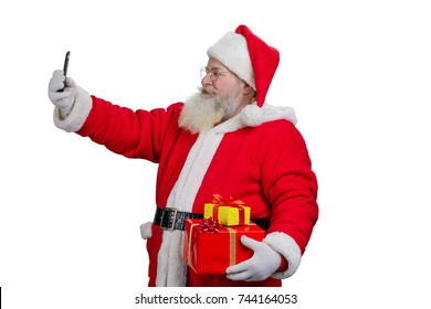 Santa Claus taking selfie with smartphone. Happy senior Santa Claus with gift boxes taking a picture with smartphone, isolated on white background.