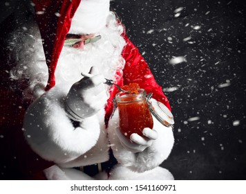 Santa Claus is taking a spoonful of red salmon caviar from a big jar, holding a fork with it under the snow. New year and Merry Christmas and happy holidays concept