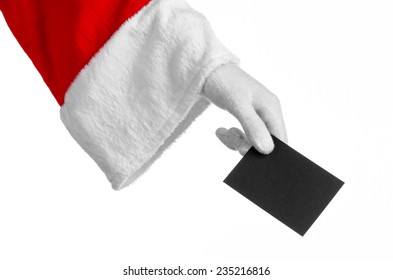 Santa Claus theme: Santa's hand holding a blank black card on a white background
