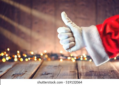 Santa Claus Thumb up gesture over Christmas holiday wooden background. Winter holiday table background decorated with Christmas garlands. Beautiful Empty Christmas room.
