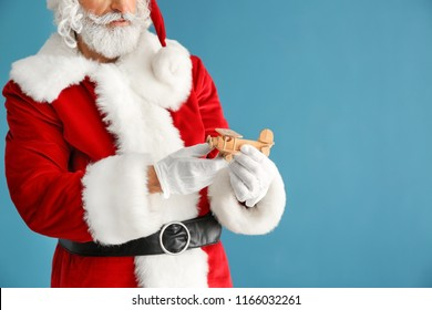 Santa Claus with toy airplane on color background