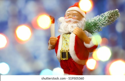 Santa Claus toy brings Christmas tree at blue snowy night bokeh  background and blurred lights foreground. Red lantern torch to light the way. Big Copyspace concept New Year`s market banner, poster.