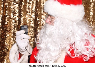 Santa Claus. Santa Claus uses the microphone of his CB Radio, Short Wave Radio or Willkie Talkie while talking to his fans around the world. Gold Sequin Background. Christmas Holiday Images.