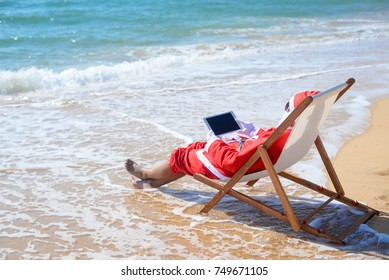 Santa Claus using tablet pc on beach tropical background. Modern internet technology holidays. Back side view of person doing xmas education project, take self photo, relaxing, play gadget or shopping
