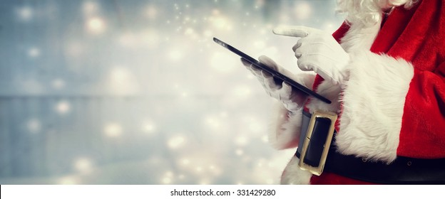 Santa Claus using a tablet in snowy night