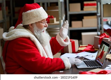 Santa Claus video calling kid talking to kid waving hand greeting on Merry Christmas, Happy New Year in virtual video online chat meeting on laptop sitting at workshop table sending gift on xmas eve.