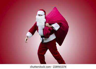 Santa Claus walking with a huge sack