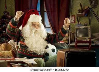 Santa Claus watching a soccer match on tv