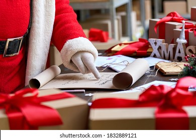 Santa Claus wearing costume reading parchment roll letter wish list standing at table with presents in workshop preparing for holiday on xmas eve. Merry Christmas wishlist background concept, closeup.
