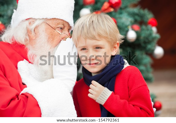 Santa Claus whispering in boy's ear outdoors
