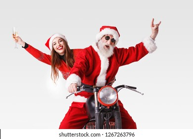 Santa Claus with white beard wearing sungasses and young mrs. Claus wearing Santa hat, red sweater and sunglasses riding a motorcycle, Mrs. Claus holding champagne and Santa Claus showing a rock
