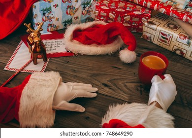 Santa Claus with white gloves holding a red mug with coffee at his wooden table with gifts, wrapping paper, Christmas hat, and correspondence.