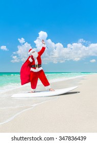 Santa Claus windsurfer on surfboard with Christmas bag come to tropical sunny beach - New Year's and Xmas active vacation concept