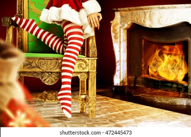 santa claus woman with xmas pantyhose on chair and interior with fireplace