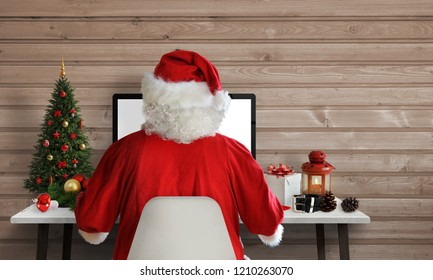 Santa Claus work on a computer in his office. Answer on letters and greeting cards via email. Free space for text beside.