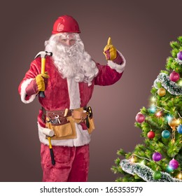 Santa Claus worker in helmet with hammer and christmas tree on brown background