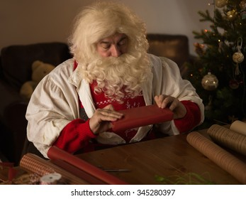Santa Claus Working at Home. Wrapping Gifts for Children