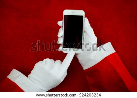 7889c8efa40da Santa Claus working using smartphone screen on red table fabric texture  background surface. Close up