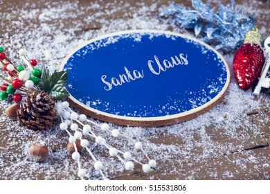 Santa Claus Written In Chalk On Blue Chalkboard Holiday Sign Background With Snow And Decorations.