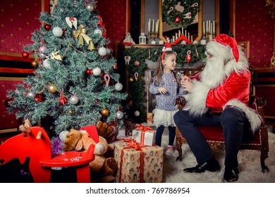 Santa Claus with your child. Christmas Scenes. Santa gives a gift in a box for a cute little girl