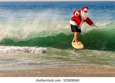 Santa Clause catching a wave on a beautiful beach. Santa hang ten. Santa surfing;