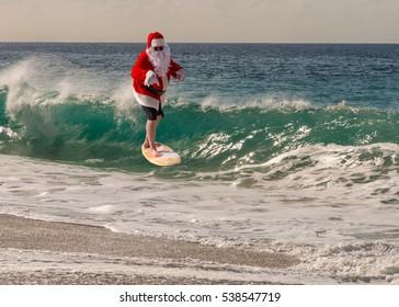 Santa Clause catching a wave on a beautiful beach. Santa hang ten. Santa surfing.